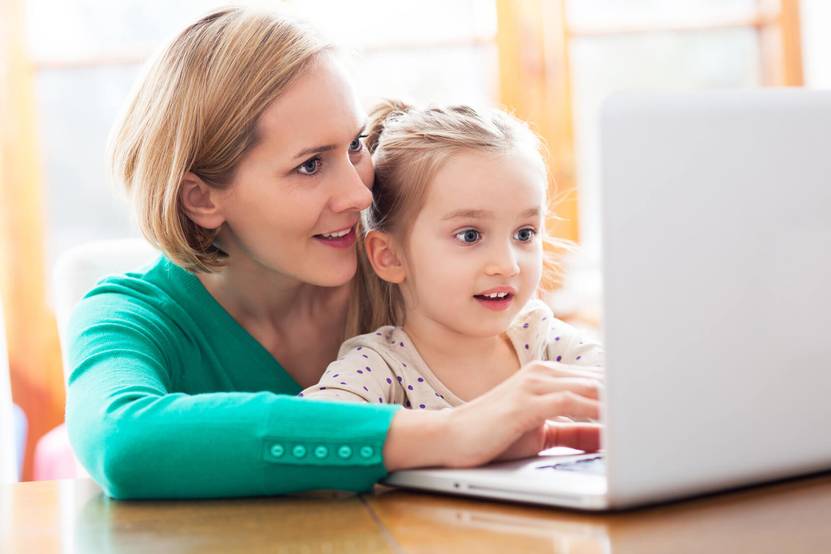 woman and daughter look at computer amazed