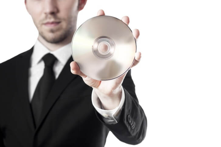 man in suit holding DVD