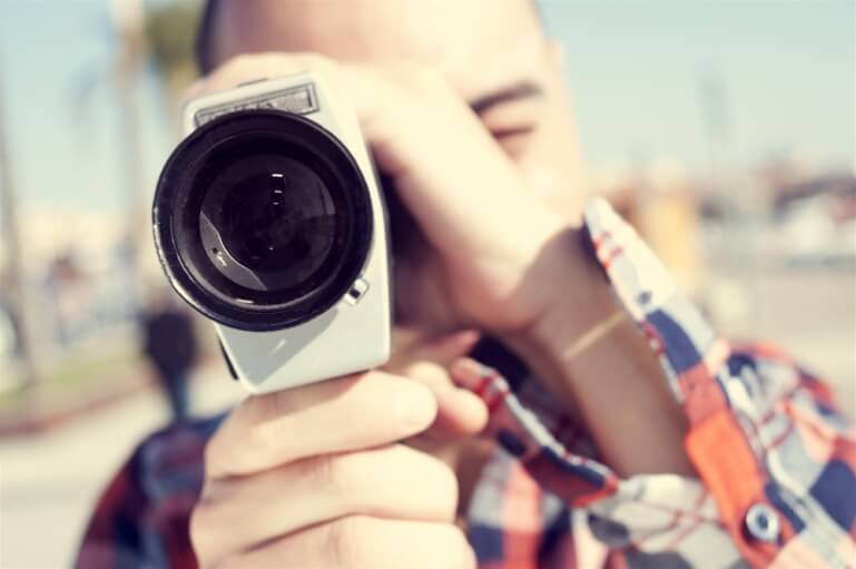 man looking through small camera lens